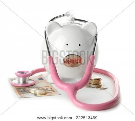 Piggy bank with stethoscope and money on white background. Health care concept