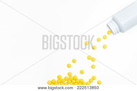 Yellow film coated tablets pills spilling out of pill bottle on white background with copy space. Painkiller tablet pills. NSAIDs pills for muscle pain.