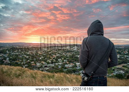 Anonymous man wearing hoody watching sunrise over Auckland city at Mount Eden view point in Auckland, North Island, New Zealand. Travel concepts