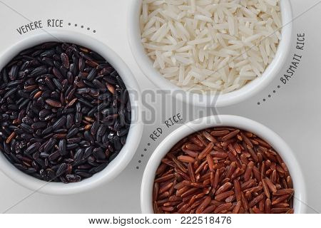 Venere rice, red rice and basmati rice in bowls on wooden background