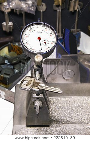 Close view of micrometer and a key in a locksmith workshop.