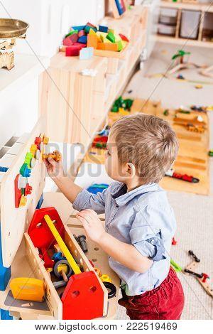 Boy plays with builder wooden instruments in the kindergarten