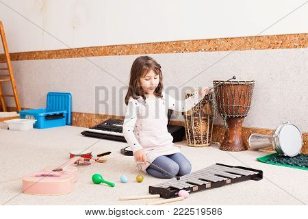 The cute little girl sits on the floor and playing on the xylophone at the kindergarten. The girl is testing various musical instruments