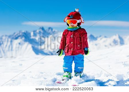 Child skiing in the mountains. Kid in ski school. Winter sport for kids. Family Christmas vacation in the Alps. Children learn downhill skiing. Alpine ski lesson for boy or girl. Outdoor snow fun.
