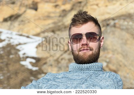Portrait of a traveler's Hipster in sunglasses and a knitted gray sweater resting against the backdrop of a winter rocks . The concept of relaxing in the mountains and trekking with walking tours