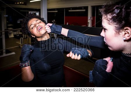 Tough female fighter punching her opponent in the face while practicing MMA in the ring