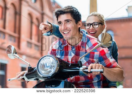 Enthusiastic young couple, woman and man, having scooter ride through Berlin