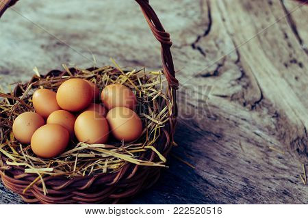 Close up of eggs in a dark brown basket.Top view of brown eggs in wooden basket.Hen eggs basket.