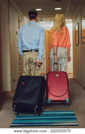 back view of middle aged couple with suitcases walking in hotel hallway
