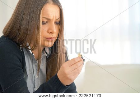 Brunette young woman holding wedding engagement ring in hands, engaged girl doubts about marriage proposal, abandoned wife depressed after getting divorced, help to overcome breaking up, starting new life, close-up