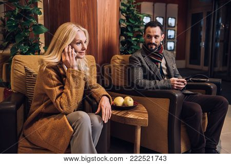 middle aged couple using smartphones while sitting and waiting in hotel hallway