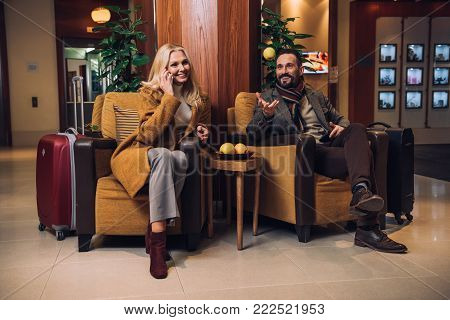happy mature couple talking and using smartphone while sitting on hotel hallway