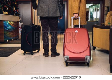 cropped shot of couple with suitcases walking at hotel hallway