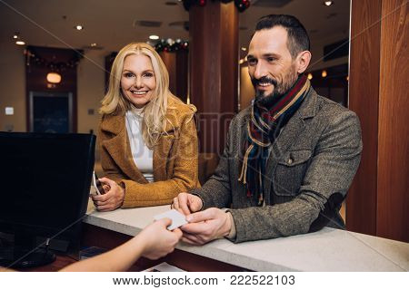 beautiful mature woman holding smartphone and smiling at camera while man taking card from receptionist