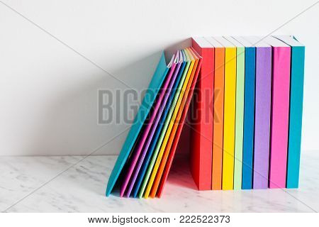 Colorful books are outlined in the colors of the rainbow. Stacked of the books on a shelf near the white wall