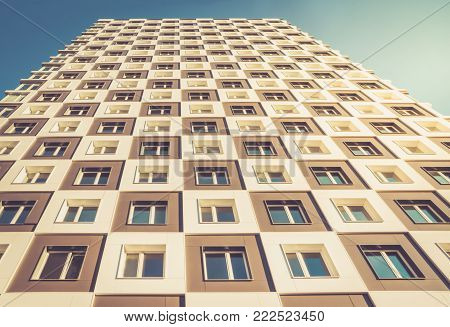From below shot of modern and new apartment building. Photo of tall block of flats against a blue sky. Golden hour.
