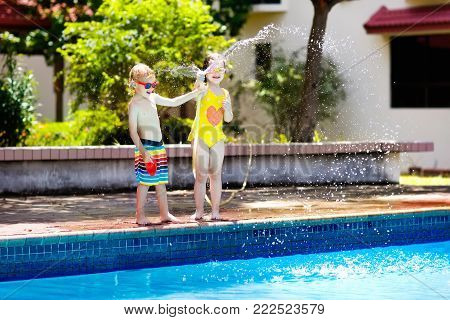 Kids playing with garden hose in backyard with large outdoor swimming pool. Children play with water. Swim wear and toys for boy and girl. Family summer vacation with hot sunny weather. Garden pool.