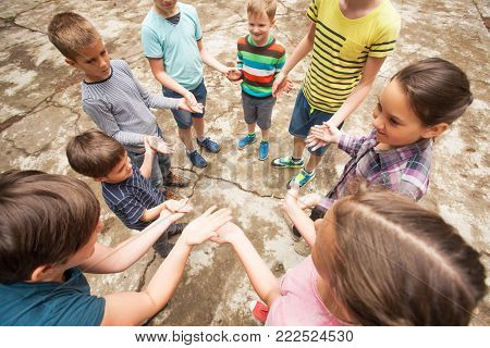 Children playing the game outdoors clapping hands  in a circle