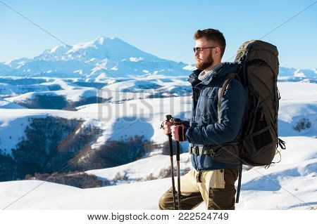 A hipster traveler with a beard wearing sunglasses in nature. A man hiking in the mountains with a backpack and Scandinavian walking sticks in the background of a mountain Elbrus landscape and blue sky. Travel lifestyle adventure outdoor recreation outdoo