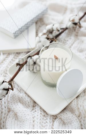 Hand-made candle with cotton branch on white cozy winter blanket, warm home decoration