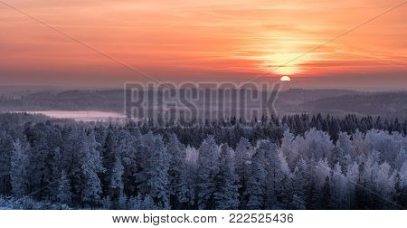 Winter landscape with frosty trees and beautiful sunset at evening time in Finland
