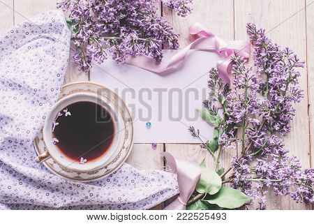 Morning Cup Of Tee, Cookies, And Lilac Flower On Wooden Table From Above. Beautiful Breakfast. Flat