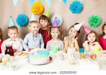 Little kids celebrating birthday. Many children near the table, friends are exciting in the hours of sweet party