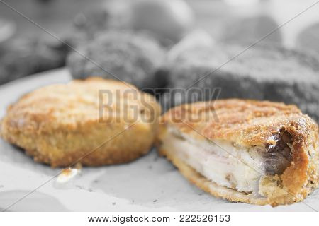 fritters stuffed with cheese and ham steak on black and white  background