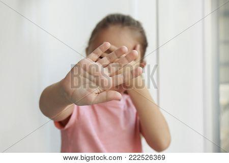 Helpless little girl hiding face. Abuse of children concept