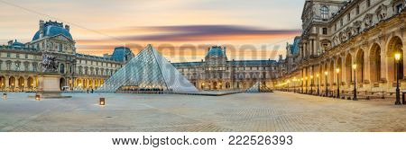 PARIS, FRANCE - DECEMBER 02, 2017: View of famous Louvre Museum with Louvre Pyramid at sunrise. Louvre Museum is one of the largest and most visited museums worldwide