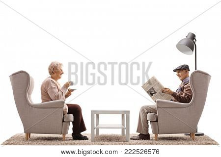 Elderly woman with a cup and an elderly man reading a newspaper seated in armchairs isolated on white background