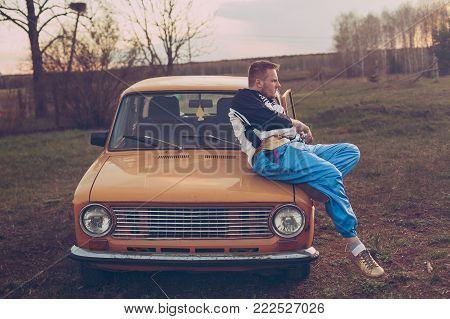 guy in the nineties lies on the hood of the old car and looks into the distance
