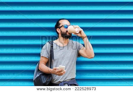 drinks, technology and people concept - man with smartphone drinking coffee from disposable paper cup on street over ribbed blue wall background