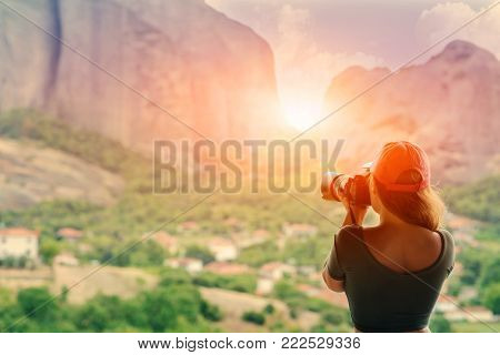 Female in red cap with camera take a picture sunset in mountain. Meteora, Greece