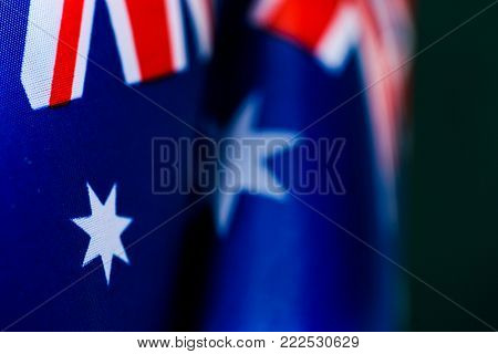 closeup of some australian flags against a dark green background