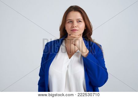 Portrait of pretty woman looking away while holding hand under chin