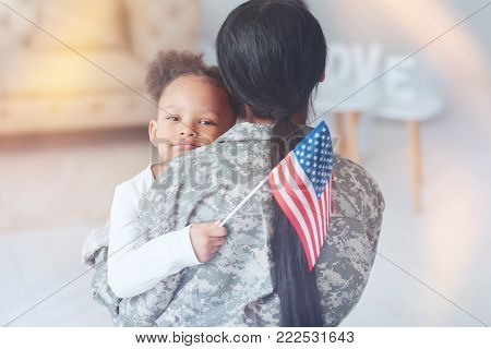 American patriot. Pleasant cute nice girl being holding an American flag and looking at you while being held by her mother