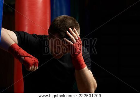 Boxing man holding head in pain after injury. Head  injury theme