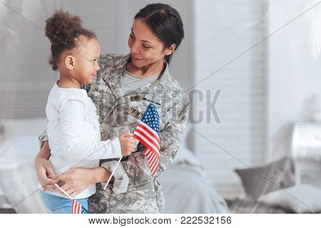 Patriotic family. Cheerful nice pleasant woman wearing a military uniform and looking at her daughter while getting ready to go on a mission