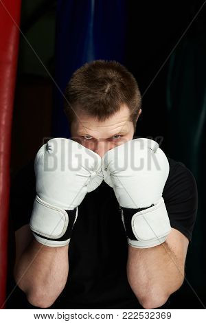 Boxer hands in gloves defending face.  Man looking through boxing white gloves