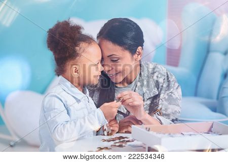Jigsaw puzzle game. Cheerful positive pretty mother and daughter holding a jigsaw puzzle piece and smiling while entertaining themselves