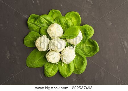 Top view of spinach with spinach gnocchi and cheese over grey background, flat lay