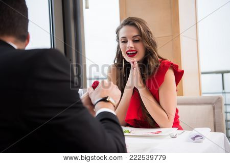 partial view of man presenting gift to girlfriend in restaurant on st valentine day