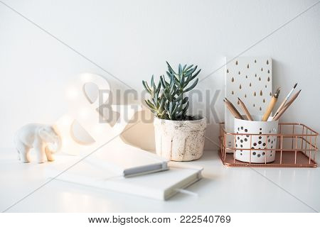White home office table, cozy and nice workplace with notepads and succulents on work desk, workspace interior