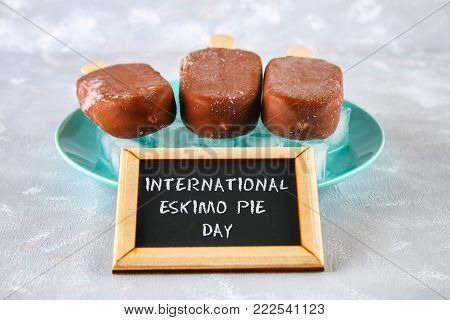 Ice cream eskimo pie on a stick with text on a gray background. Concept for the holiday International Eskimo pie day