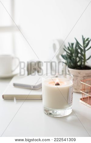 White burning candle on table, home interior decorations in daylight