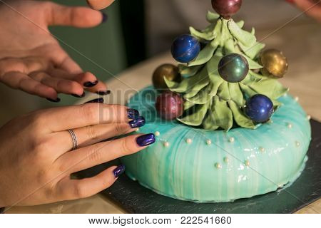 Colorful icing on the cakes. Modern French mousse cake with mirror glaze. Woman hands decorating dessert with chocolate christmas tree. Culinary art.