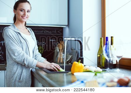 Beautiful young woman washing vegetables for salad while standing in the kitchen.