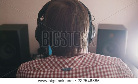 Young guy composer composes music on the computer, sound engineer working, back view