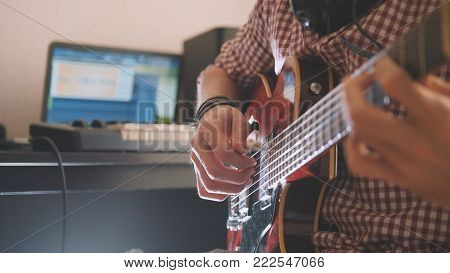 Young musician composes and records music playing the guitar, using computer and keyboard, focus on hands